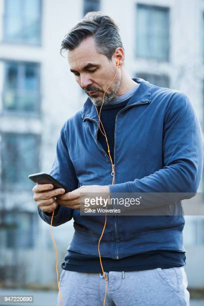 portrait of a mature man listening to a podcast while stretching - männer über 30 stock-fotos und bilder