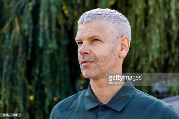 portrait of a mature man outdoors looking sideways - seitenblick stock-fotos und bilder