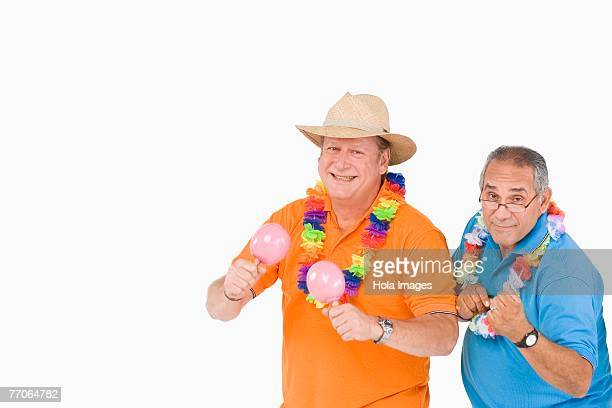 portrait of a mature man playing maracas and his friend standing beside him - maraca stock photos and pictures