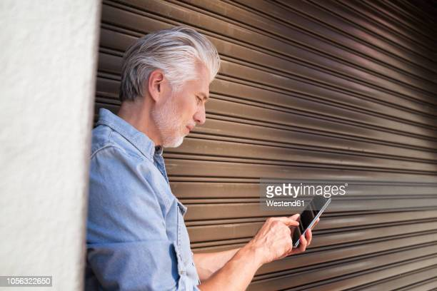 portrait of a mature man, using smartphone - roller shutter stock pictures, royalty-free photos & images