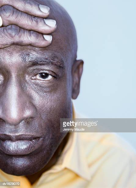 Portrait of a Mature Man wearing a Yellow Shirt with a Hand on His Head looking Depressed
