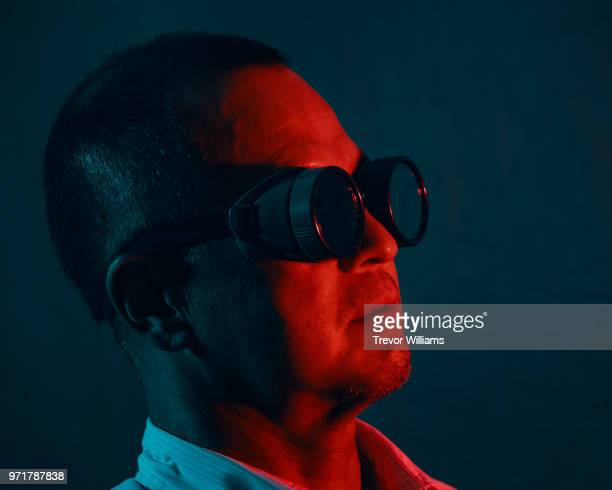 Portrait of a mature man wearing goggles under a red and blue light