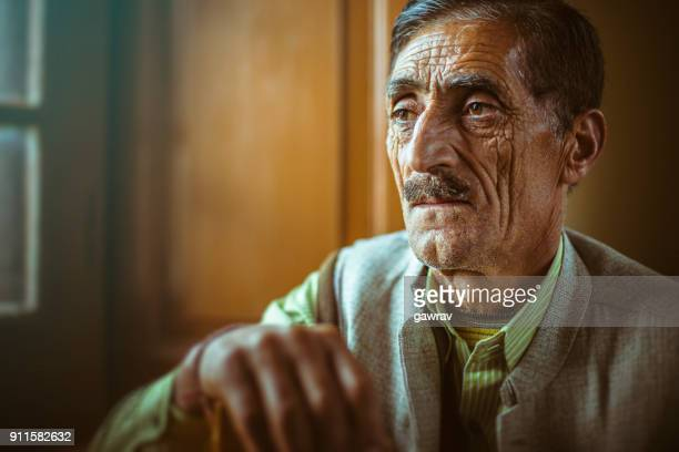 Portrait of a mature men sitting near window and thinking.