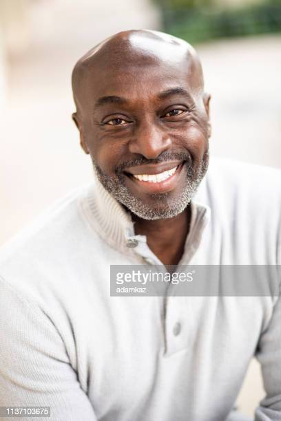 Portrait of a Mature Senior Black Man Sitting and Laughing