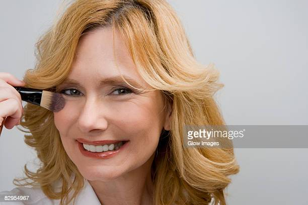Portrait of a mature woman applying blush on her cheek and smiling