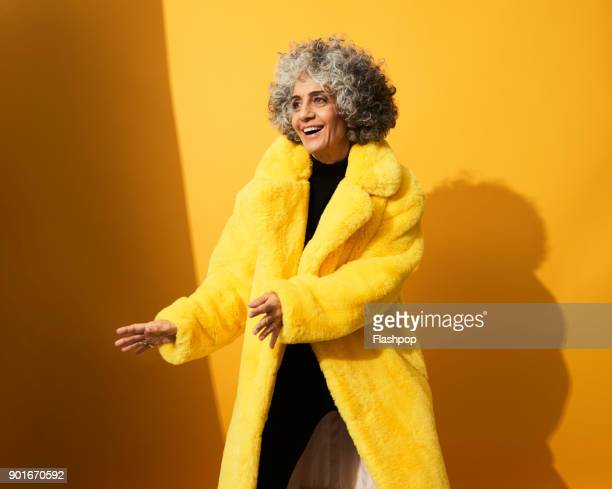 portrait of a mature woman dancing and laughing - coat fotografías e imágenes de stock
