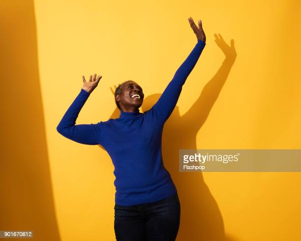 portrait of a mature woman dancing and laughing - dancing stock photos and pictures