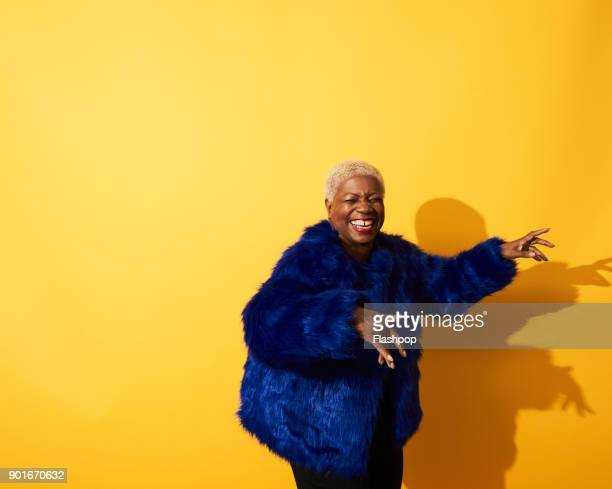 portrait of a mature woman dancing and laughing - navy blue stock pictures, royalty-free photos & images