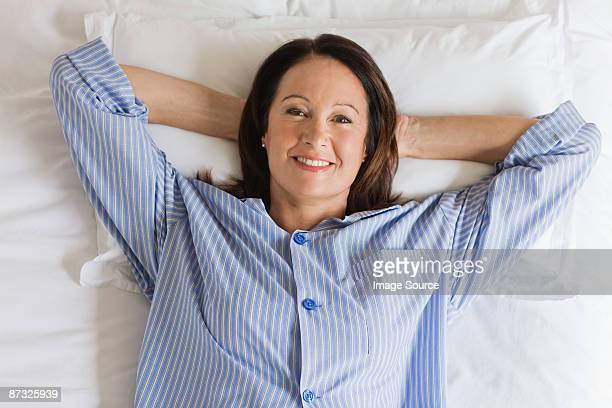 portrait of a mature woman having breakfast - pyjama stockfoto's en -beelden