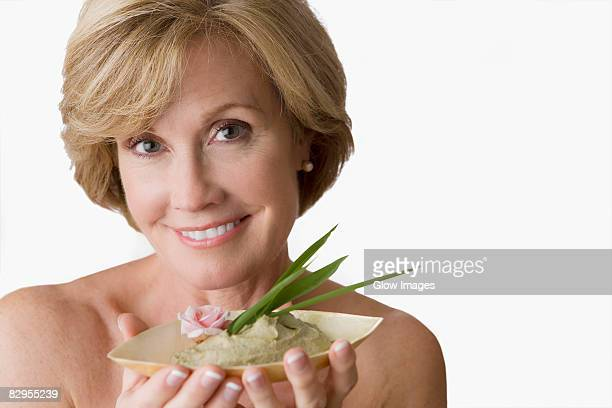 Portrait of a mature woman holding a bowl of face pack