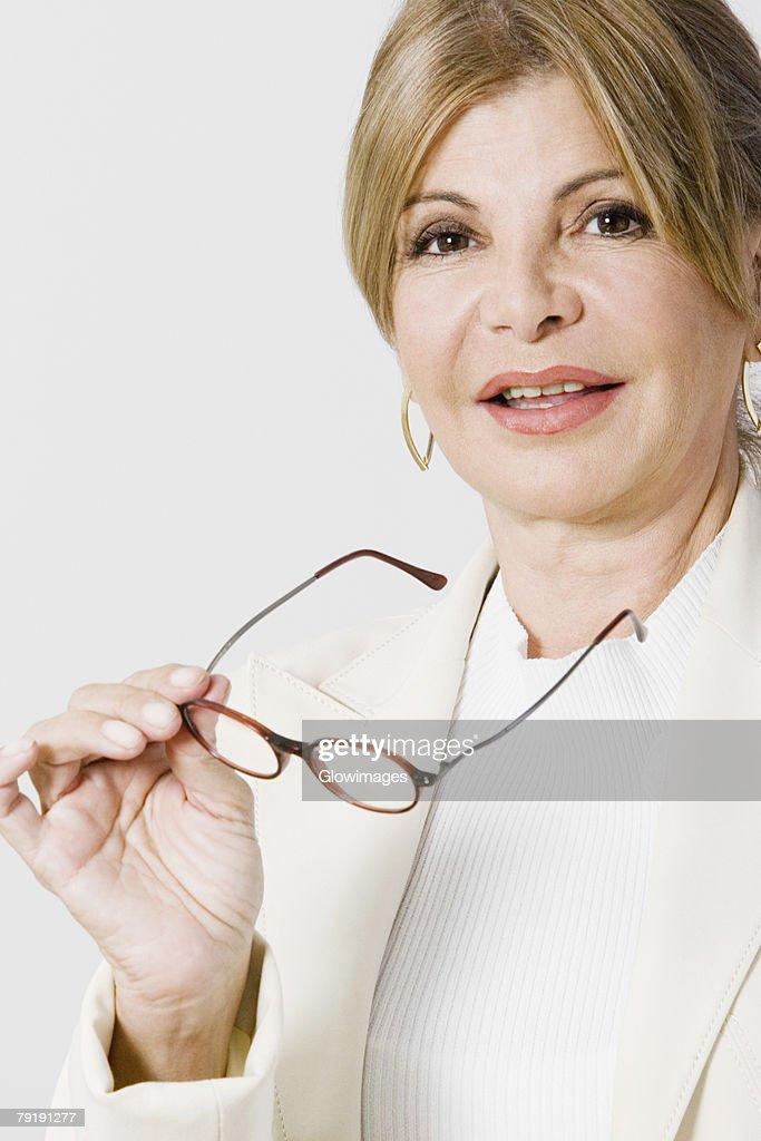 Portrait of a mature woman holding eyeglasses : Foto de stock