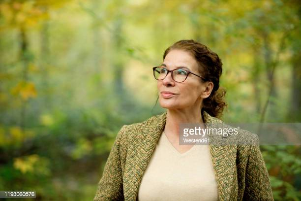 portrait of a mature woman in a autumn forest - 雰囲気 ストックフォトと画像
