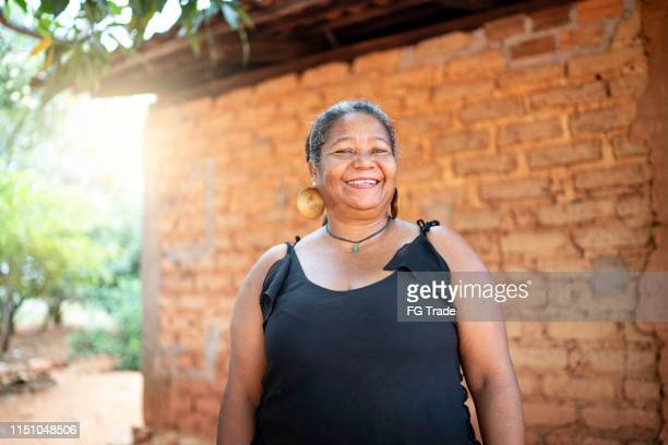 portrait of a mature woman in front of a wattle and daub house - humility stock pictures, royalty-free photos & images