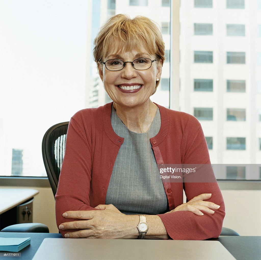 portrait of a mature woman in glasses sitting in an office stock