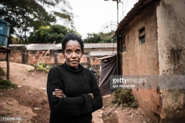 retrato de uma mulher madura em sua vizinhança - pobreza questão social - fotografias e filmes do acervo