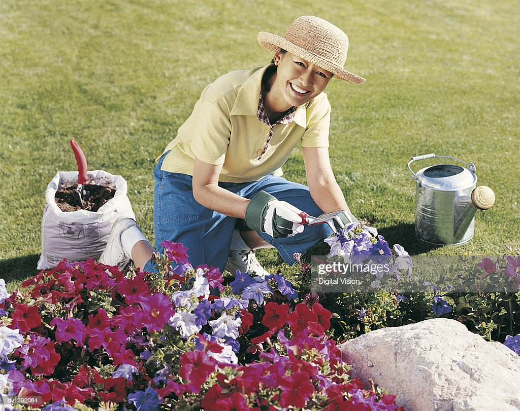 Portrait of a Mature Woman Kneeling at a Flowerbed in Her Garden and Holding a Gardening Fork : Stock Photo