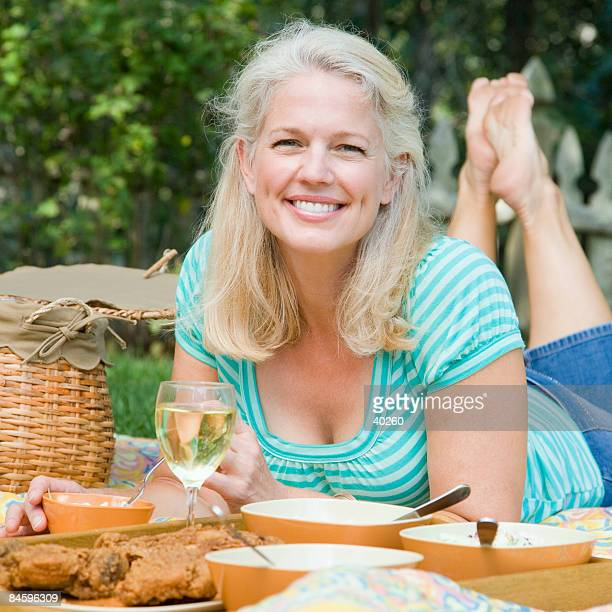 portrait of a mature woman lying on a picnic blanket and smiling - soles pose stock pictures, royalty-free photos & images