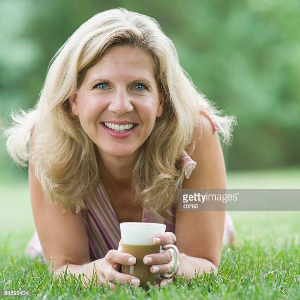 Portrait of a mature woman lying on grass and holding a coffee cup