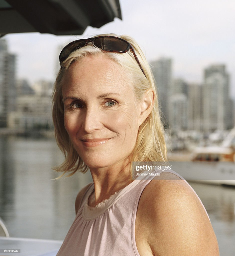 Portrait of a Mature Woman Outdoors With Sunglasses Raised on Her Head :  Stock Photo
