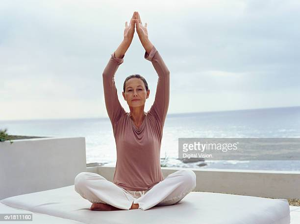 Portrait of a Mature Woman Sitting in the Lotus Position With Her Arms Up on a Balcony by the Sea