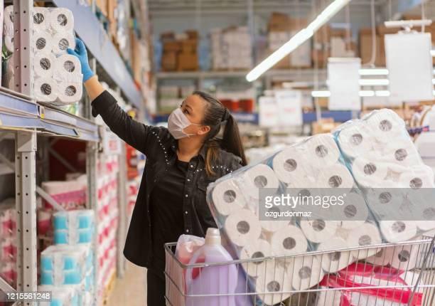 portrait of a mature woman wearing a protective mask shopping in a supermarket - panic buying stock pictures, royalty-free photos & images