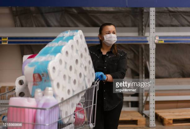 portrait of a mature woman wearing a protective mask shopping in a supermarket - buying toilet paper stock pictures, royalty-free photos & images