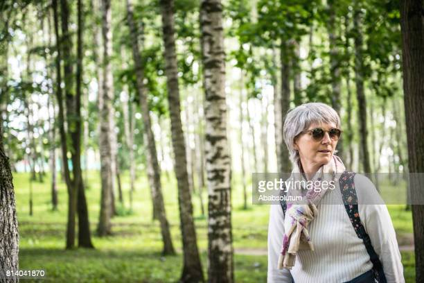 Portrait of a Mature Woman with Backpack in Birch Forest, Dubna, Russia