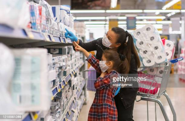 portrait of a mature woman with her daughter wearing a protective mask shopping in a supermarket - buying toilet paper stock pictures, royalty-free photos & images