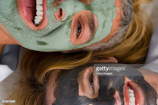 Portrait of a mature woman with her daughter wearing facial masks and smiling