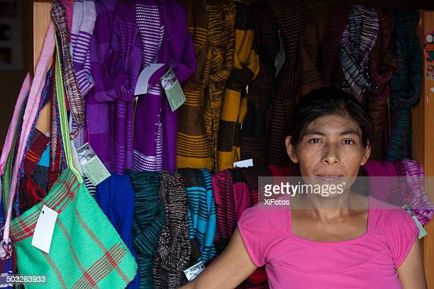 Portrait of a Mayan woman in front of woven textiles.