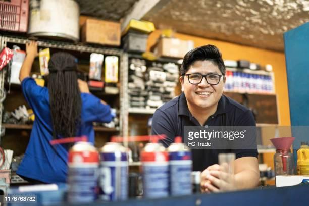 retrato de um mecânico que trabalha em uma auto loja de reparo - pequeno - fotografias e filmes do acervo