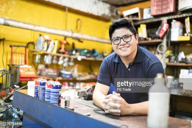 portret van een monteur die in een auto reparatiewerk winkel werkt - mid volwassen mannen stockfoto's en -beelden