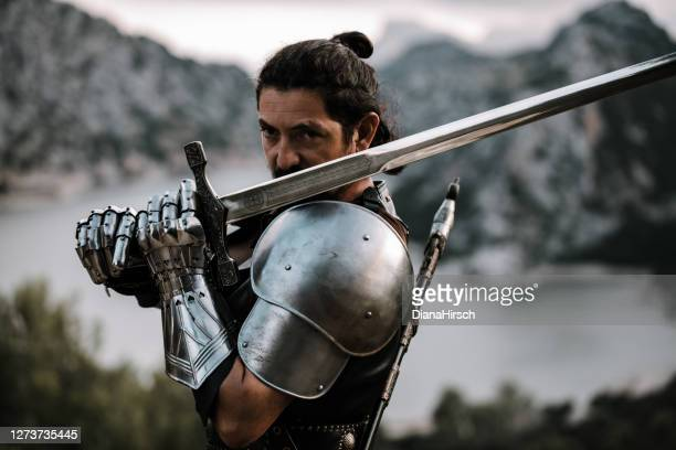 portrait of a medieval knight in front of an amazing landscape with sea - sword stock pictures, royalty-free photos & images
