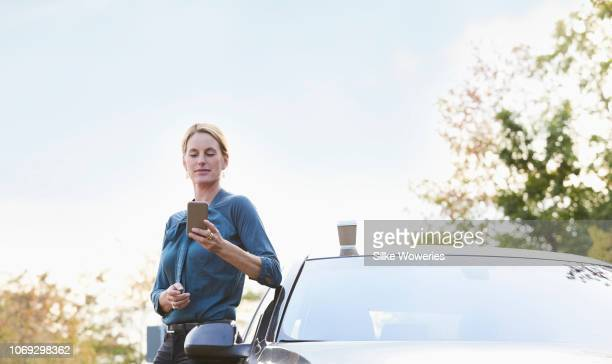 portrait of a mid adult businesswoman leaning against her car reading text messages - next to stock pictures, royalty-free photos & images