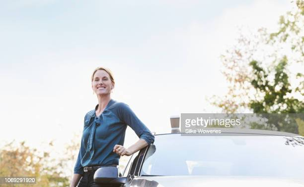 portrait of a mid adult businesswoman standing beside her car - next to stock pictures, royalty-free photos & images