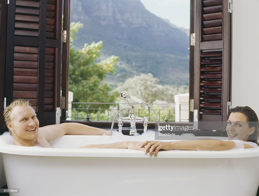 Portrait of a mid adult couple bathing in a bathtub and smiling : Stock Photo