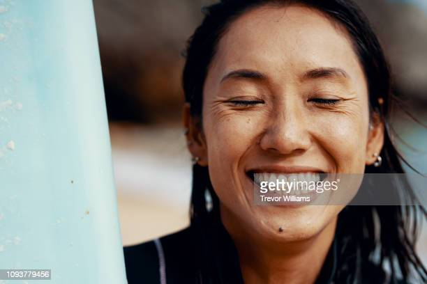portrait of a mid adult female athlete with her surfboard and showing a positive emotion - 満足 ストックフォトと画像