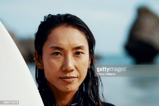 portrait of a mid adult female athlete with her surfboard standing on a beach - asia pacífico fotografías e imágenes de stock