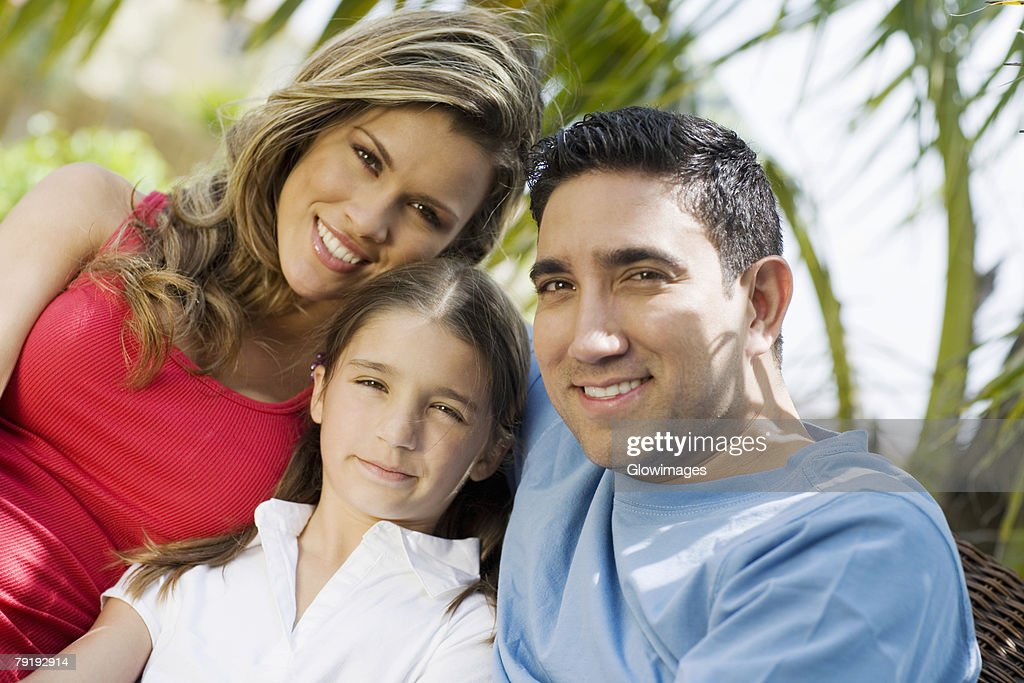 Portrait of a mid adult man and a young woman smiling with a girl : Stock Photo