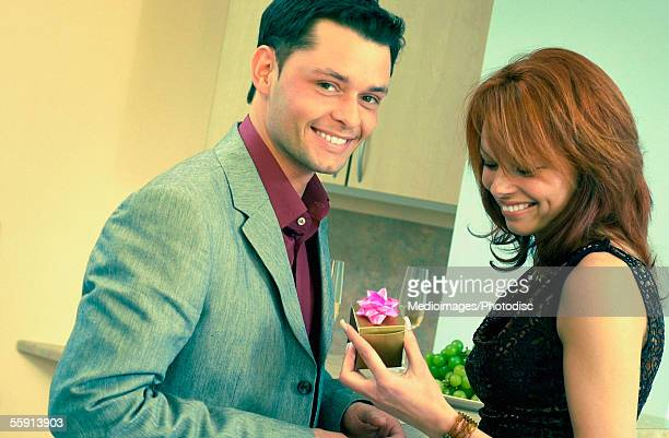 Portrait of a mid adult man giving a present to a mid adult woman