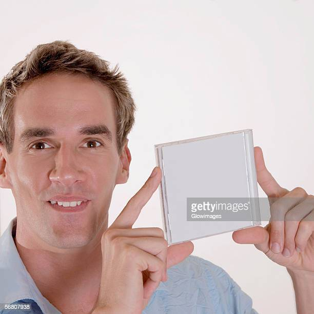 Portrait of a mid adult man holding a CD case