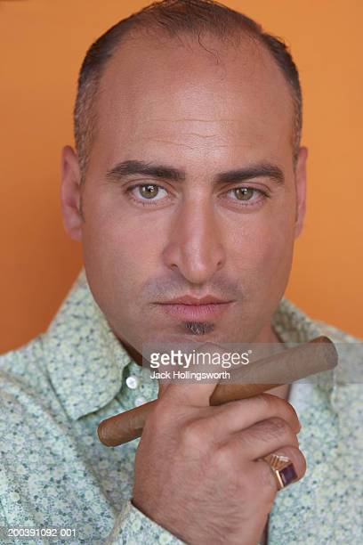 Portrait of a mid adult man holding a cigar