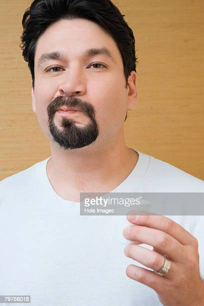 Portrait of a mid adult man holding a cup of mouthwash and rinsing his mouth with mouthwash
