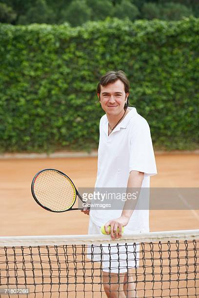 Portrait of a mid adult man holding two tennis balls and a tennis racket