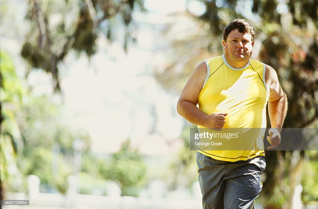 portrait of a mid adult man jogging in a park : Stock Photo