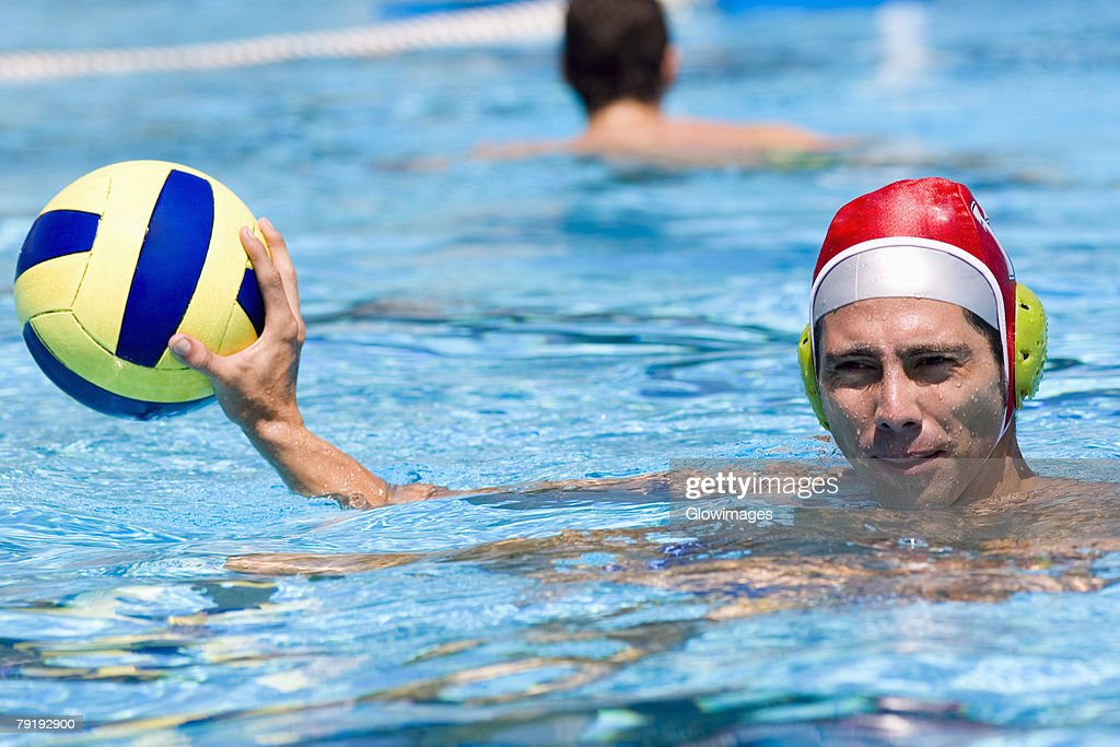 Portrait of a mid adult man playing water polo in a swimming pool : Stock Photo