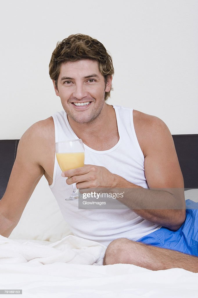 Portrait of a mid adult man sitting on the bed and holding a glass of orange juice : Stock Photo