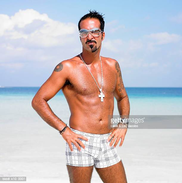 Portrait of a mid adult man standing on the beach with arms akimbo