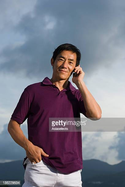 Portrait of a mid adult man talking on a mobile phone and smirking