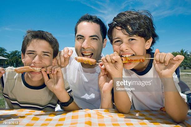 Portrait of a mid adult man with his two sons eating sausages in a picnic